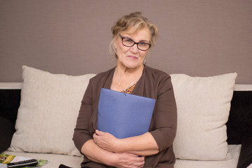 Old woman in glasses with a folder holding hands
