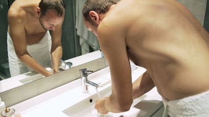 Young man in towel washing his face after shower in bathroom
