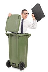 Terrified businessman hiding in a trash can
