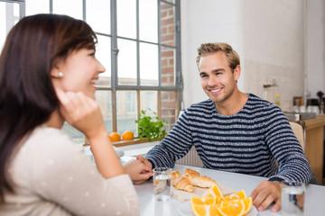 lachendes paar hält händchen am küchentisch