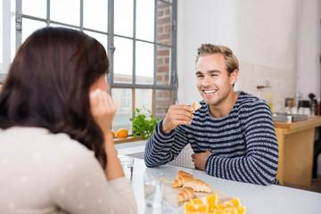 glückliches paar unterhält sich am küchentisch