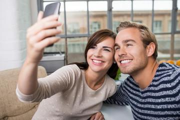 lachendes paar macht ein foto mit dem handy