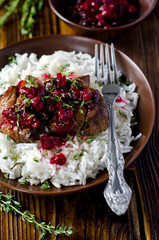 Meat with cranberry sauce and garnished with rice