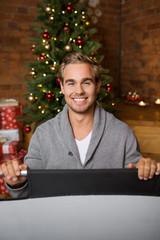 lachender mann vor dem weihnachtsbaum hält ein schild