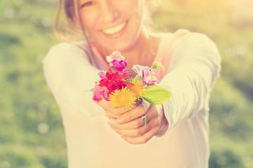 Smiling girl holding flowers.
