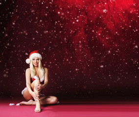 Young, sexy and beautiful female Santa over Christmas background
