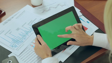 Business woman drives a finger on a tablet monitor with a green