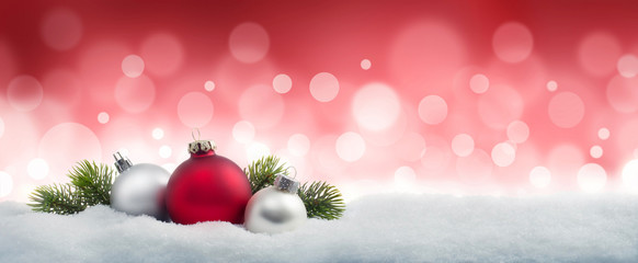 Weihnachtskugeln im Schnee vor Rot