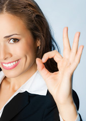 Happy business woman with okay gesture, over blue