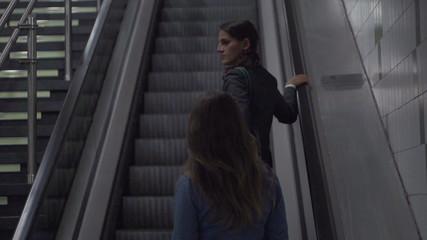 Businesswomen riding by escalator, slow motion 240fps, steadycam