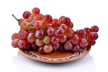 Czerwone winogrona na ceramicznym talerzu