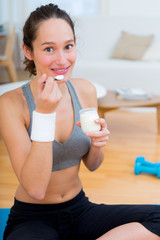 Attractive sportive woman eating yoghurt after sport