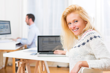 Young attractive blonde woman working on computer