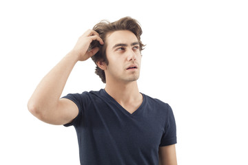 Young man scratching his head