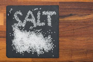 Grobes Salz auf schwarzem Schiefer mit Holzhintergrund