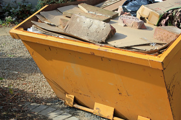 Close-up of yellow skip full of concrete and rubbish
