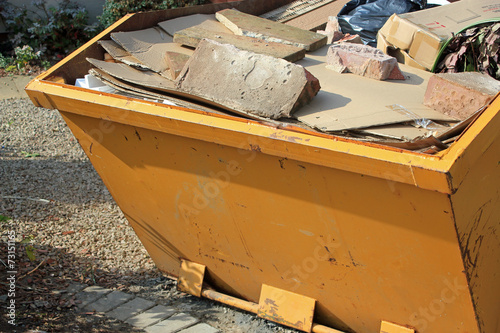 Close-up of yellow skip full of concrete and rubbish - 73151165