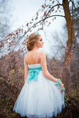Redhead bride in short dress in the autumn field
