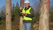 Happy Forest engineer with tablet PC near the trees