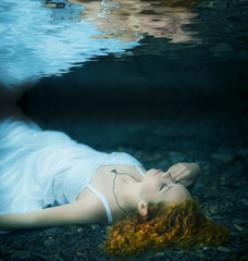 Young redhead beautiful woman lying underwater.
