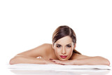 Fototapety Portrait of beautiful young woman lying down on towel