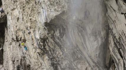 rock climber on steep cliff next to Vanturatoarea waterfall