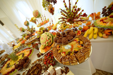 Colorful fruits and cakes on table at a wedding