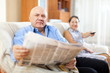 mature couple together with newspaper