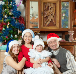 family with little girl in santa hats in Christmas