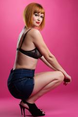Slim redhead model posing on pink background