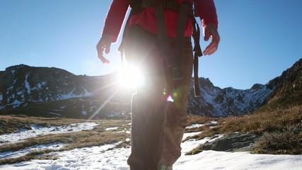 Hiker descending mountain trail at sunset