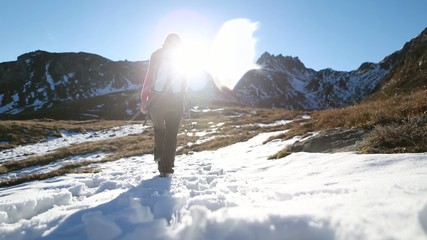 Hiker walks towards mountain peak at sunrise, arms outstretched
