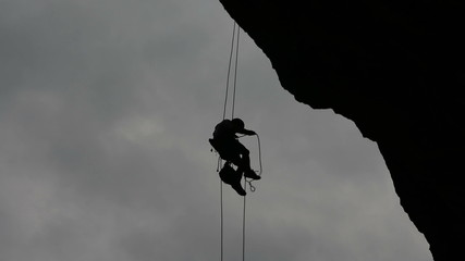 Rock climber hanging in space backlight