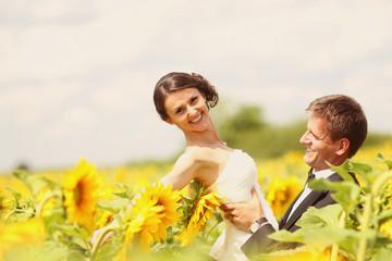 Beautiful couple having fun in sunflowers fields