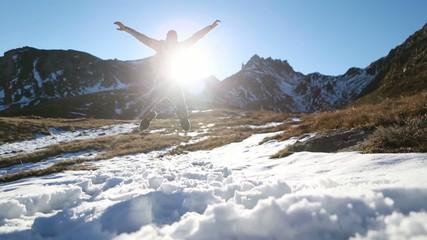 Hiker walks towards mountain peak, jumps