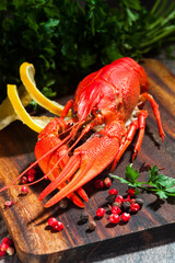 Boiled crayfishes on cutting board with lemon, pepper and parsle