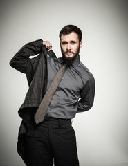 Handsome man with beard putting on jacket