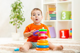 funny child playing with color toy indoor poster