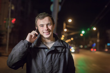 Portrait of the young man in the street night city with phone