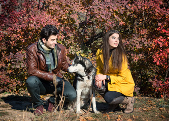 Young couple with their husky dog resting in autumn countryside