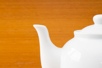 Close up white teapot on wooden table