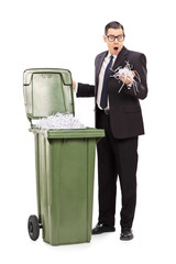Shocked businessman looking into a trash can