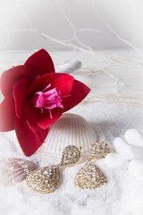 Diamond earrings in the sand with red flower