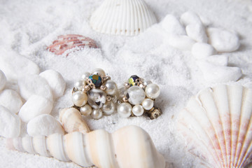 Pearl earrings in the sand with seashells