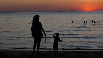 Silhouette of Mother and Son by the Sea at Sunset.