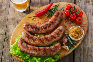 Grilled sausage on a board with vegetables and sauce