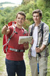 Two Young Men Hiking In Countryside Together