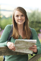 Portrait Of Woman Hiking In Countryside Looking At Map