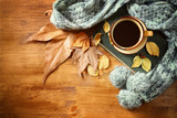 Fototapety Top view of Cup of black coffee with autumn leaves, a warm scarf