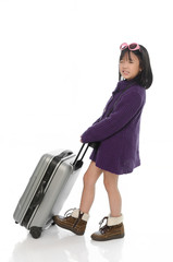 Little asian girl pulling heavy baggage